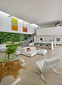 White, modern, open-plan interior with glass wall leading to garden