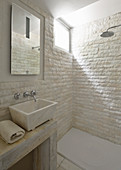 Stone tiles and marble countertop sink in bright bathroom