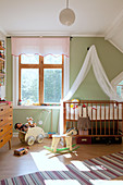 Cot with canopy in vintage-style nursery with green walls