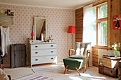 Retro furniture and old suitcases in vintage-style bedroom