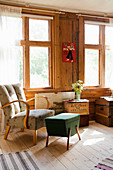 Retro armchair and footstool with storage compartment in front of windows in wooden wall