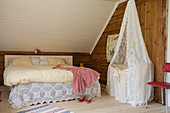 Cot under lace canopy next to double bed below sloping ceiling