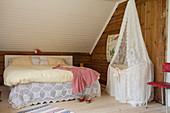 Babybett mit Spitzenbaldachin neben dem Elternbett unter der Schräge