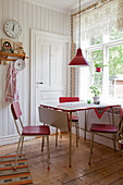 Red retro chairs around table below window in country-house kitchen