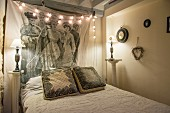Fairy lights, antique bedside lamps and wall hanging in vintage bedroom