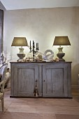 Two table lamps and peace dove ornament on vintage sideboard
