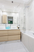 Bathtub with glass screen and twin washstand in elegant bathtub with marble tiles