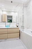 Badewanne mit Glasabtrennung und Doppelwaschtisch in elegantem Badezimmer mit Marmorfliesen