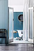 Blick durch geöffnete Saloontüren in blau-weißes Bad eines Strandhauses