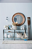 Round wall mirror over a half-high shelf with maritime decorative objects