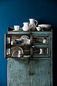 Porcelain collection in a blue vintage buffet cabinet