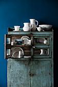 Porzellansammlung in blauem Vintage-Buffetschrank