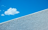 Fluffy cloud in blue sky seen over diagonal white wall