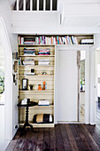 Bookshelf around sliding door, in front of antique, round side table
