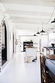 Offene, weiße Küche mit Vintage Einrichtung in ehemaliger Kirche