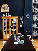 Dining table with chairs and display cabinet made of wood in an open living room with a dark blue wall