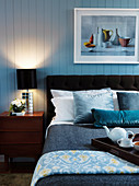 Double bed and bedside table with bedside lamp in the bedroom with wooden paneling