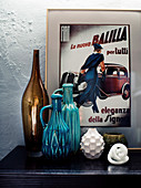 Decorative objects, vase and ceramic jugs in front of a retro advertising poster