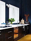 Kitchenette in front of white louvre windows in a high kitchen with a dark blue wall