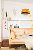 Bright leather couch with fur blanket and floor lamp in front of sideboard