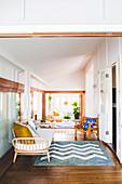 Bank mit Polsterauflage und Kissen, Klassikerstuhl und Teppich mit Zig-Zag-Muster