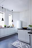 weiße Einbauküche mit schwarzen Pendelleuchten vor dem Fenster