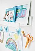 Kinderzeichnungen auf Wandboard und an einer Wäscheleine hängend im Kinderzimmer