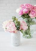 Rosa Pfingstrosen in zwei Vasen