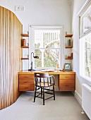 Alter Windsorstuhl vor modernem Schreibtisch neben runder Wand
