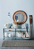 Large round mirror over maritime-decorated console table