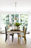 Various brightly coloured chairs around dining table in front of large lattice window
