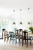 Drei Deckenleuchten über Esstisch mit verschiedenen bunten Stühlen