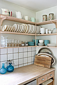 Plate racks and blue crockery on wall-mounted kitchen shelves