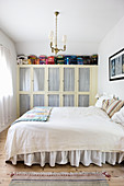 Bed with ruffled valance in front of old fitted wardrobes with glass door panels
