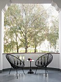 Two black Acapulco chairs and small side table on balcony with view of trees