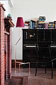 Gemauerter Kamin in Musikzimmer mit schwarzem Klavier und Stehleuchte
