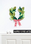 Hand-made wreath of paper leaves with red and white gingham ribbon