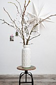 DIY-Girlande aus weißen Papierkugeln um Äste in weißer Vase