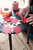 Hands sticking red dot on cut-out paper stars