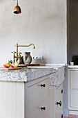Stone worksurface and sink in country-house kitchen