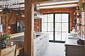 Kochinsel vor Terrassentür in der Küche mit Ziegelwand und Holzstützen