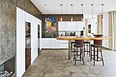Grosszügige Küche mit weissen Hochglanzschränken und beschichteter Wand, in der Mitte Thekentisch mit rustikaler Tischplatte
