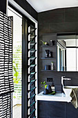 Modern bathroom in black with slate tiles and louvre windows