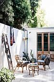 Korbstühle und Holzleiter auf der sonnigen Terrasse im Innenhof