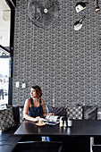 Woman sitting in the restaurant with black and white patterned wallpaper