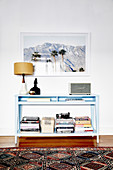 Blue console table with piles of books under the framed photo