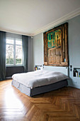 Old weathered wooden door on pale blue wall above bed