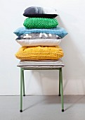 Stacked cushions with hand-made covers on green metal stool