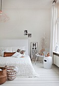 White feminine bedroom decorated with copper-coloured accessories and vintage eye chart
