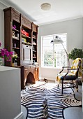 Large hand-crafted bureau and zebra-skin rug in living area